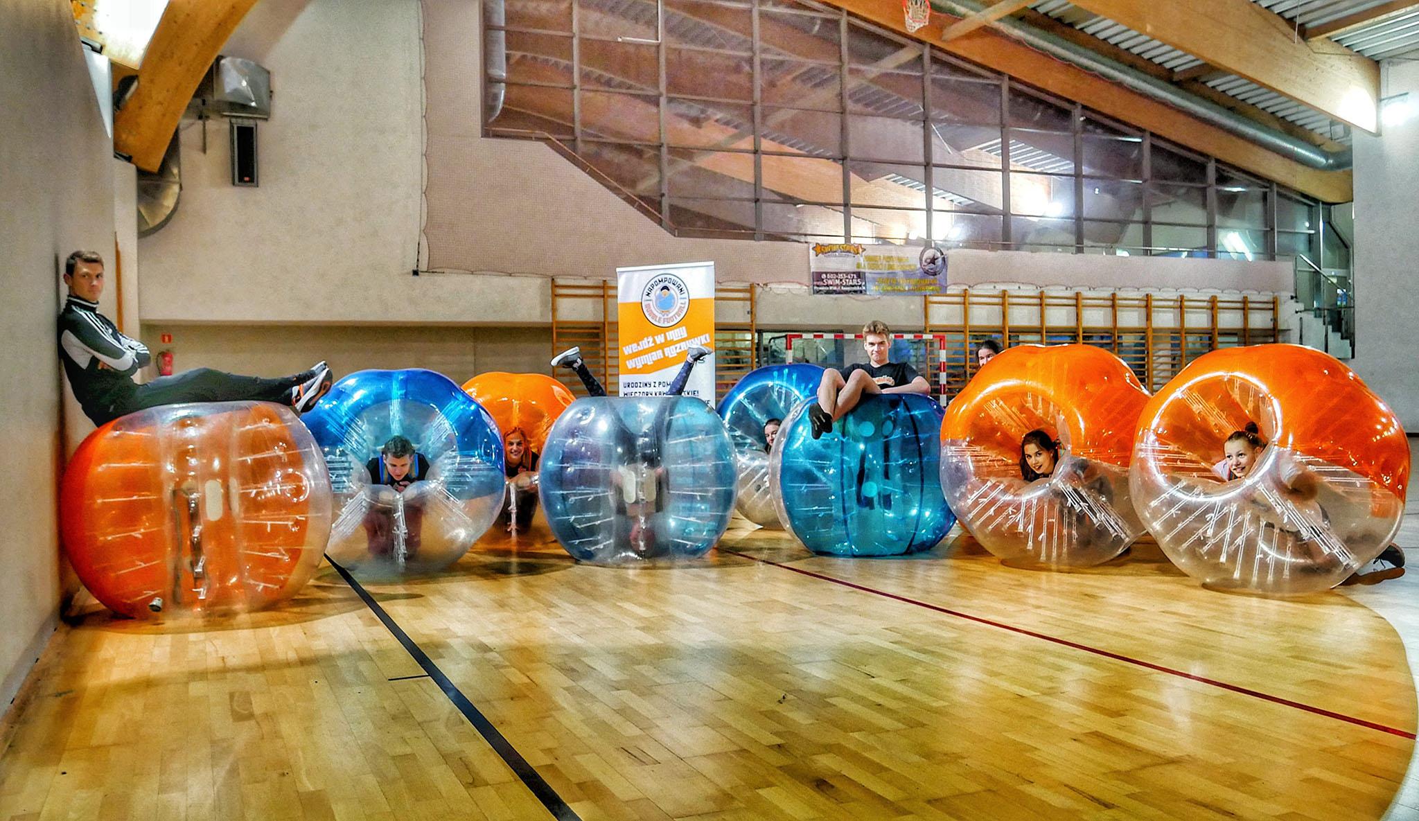 Dzieci w pomarańczowych i niebieskich kulach Bubble Football z trenerem